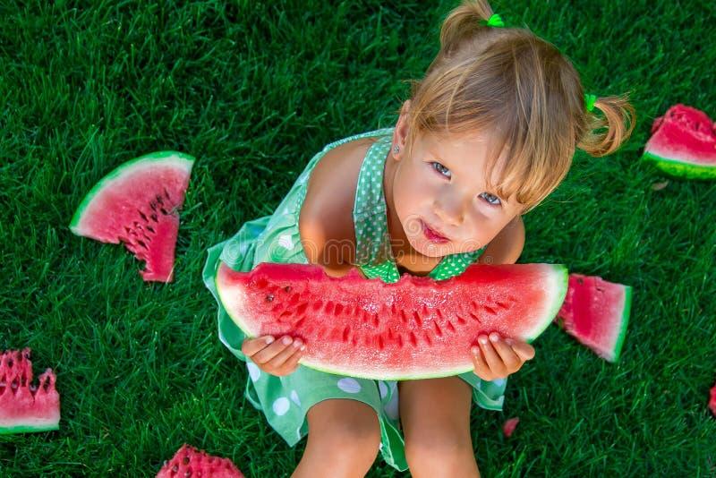 Kindzitting op het gras met plakken van watermeloen in de zomer het bekijken camera stock afbeeldingen