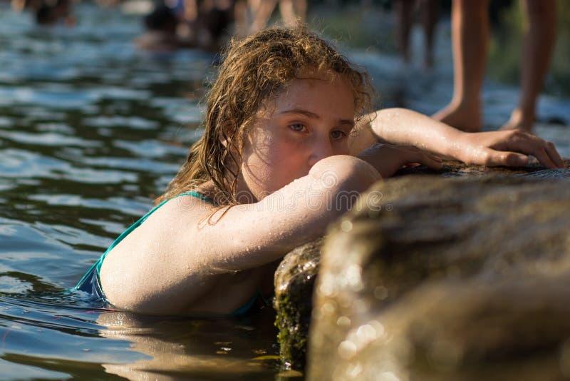 Kindzwemmer die tegen rivierbank leunen stock foto
