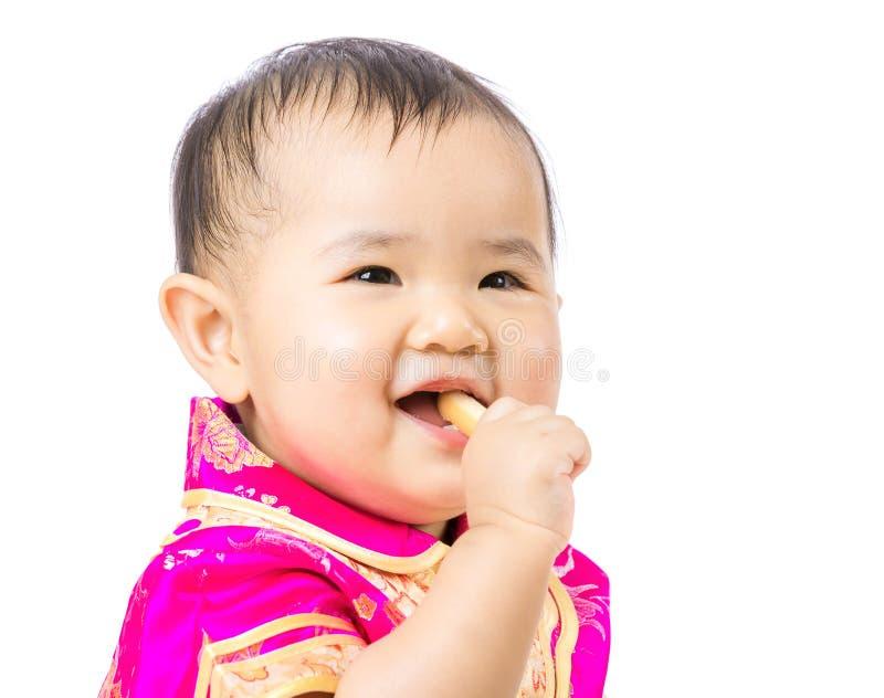 Kines behandla som ett barn äta kexet arkivbild