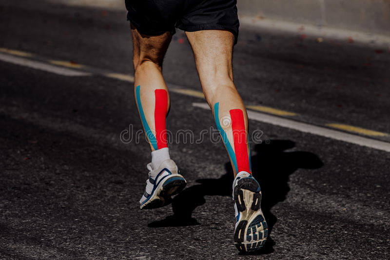 Kinesio taping on muscles of calf male athlete. Running marathon stock photos