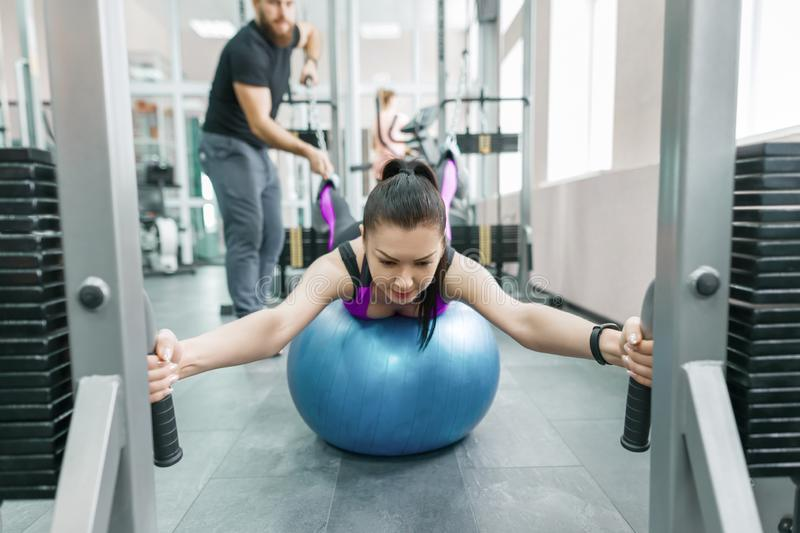 Kinesis technology, kinesitherapy, healthy lifestyle. Young woman doing rehabilitation exercises with personal instructor using royalty free stock images
