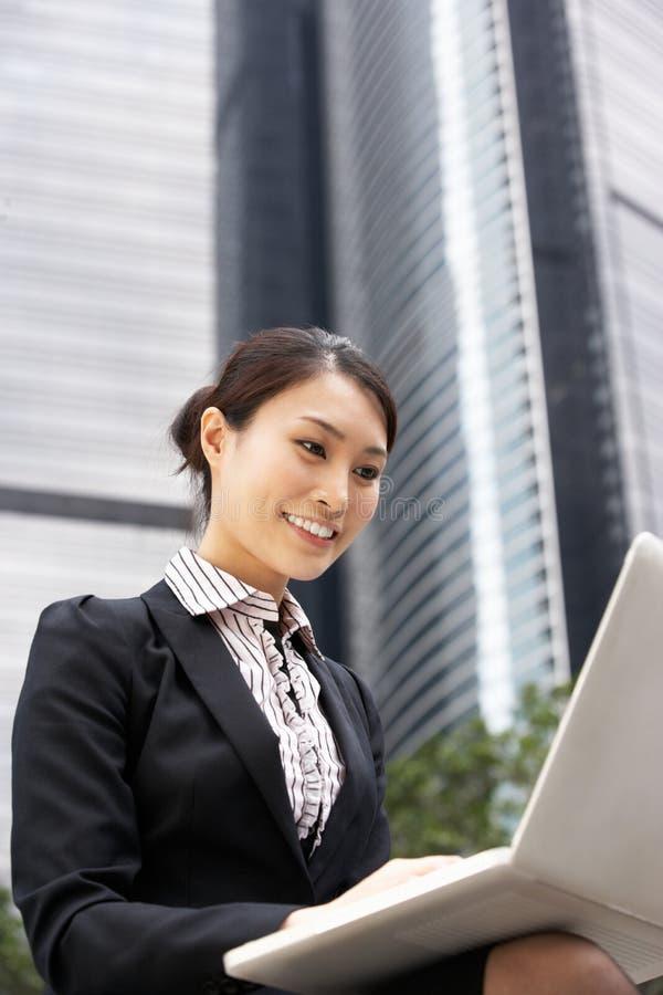 Kinesisk affärskvinna som fungerar på bärbar dator royaltyfria foton