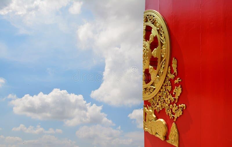 Kinesisk dörr, blå himmel för röd kinesisk tempeldörr med molnbakgrund royaltyfri bild