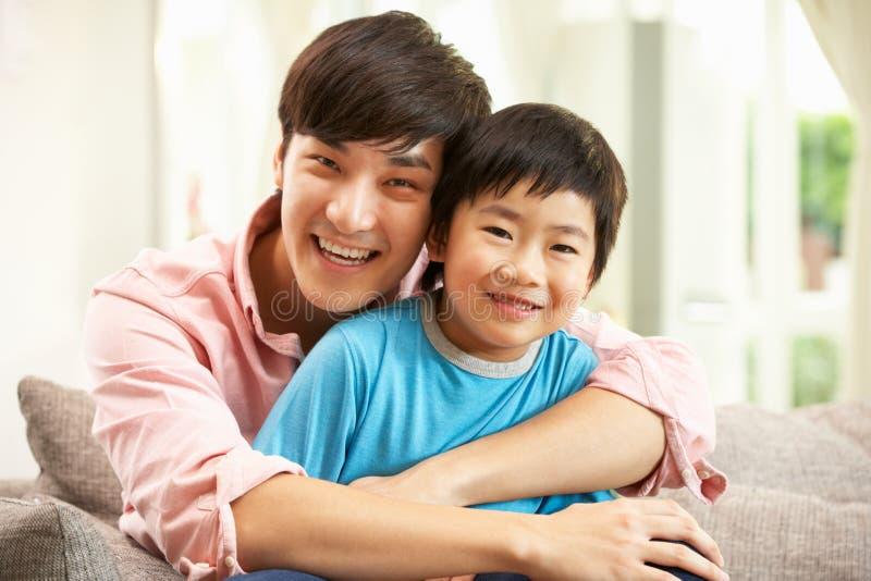 Kinesisk fader och Son som hemma kopplar av på sofaen fotografering för bildbyråer