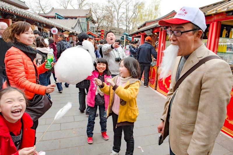 Kinesisk familj har kul med bomullsgodis Fader med kejsarskägg av bomullskandy arkivfoto