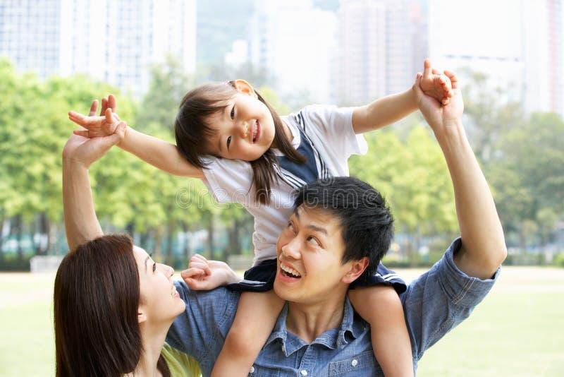 Kinesisk familj som ger dotterritt på skulder fotografering för bildbyråer