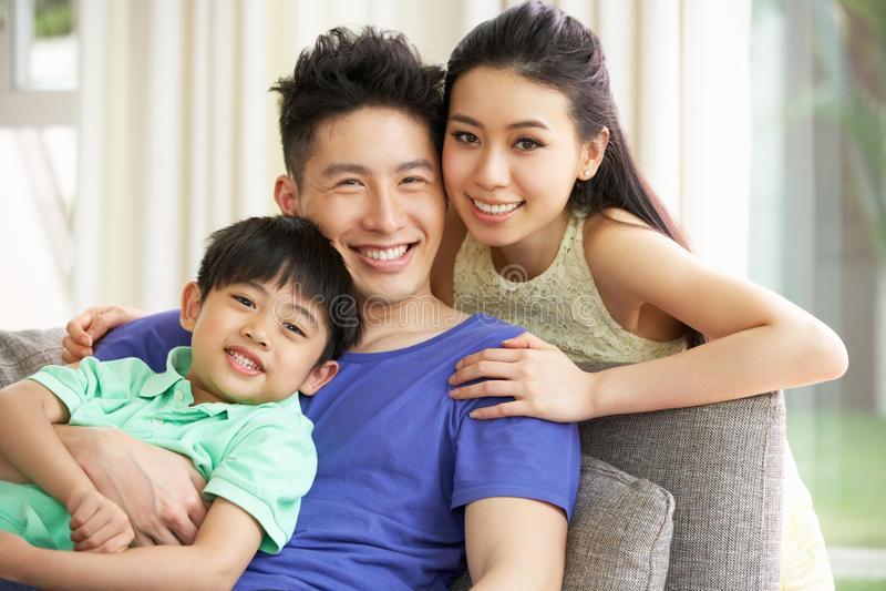 Kinesisk familj som sitter och kopplar av på sofaen royaltyfri fotografi