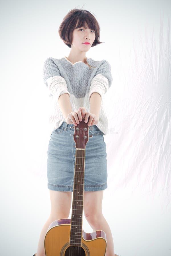 Kinesisk flicka och gitarr fotografering för bildbyråer