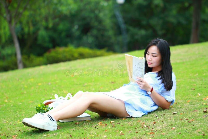 Kinesisk flicka som läser boken Blond härlig ung kvinna med boken som ligger på gräset arkivbild