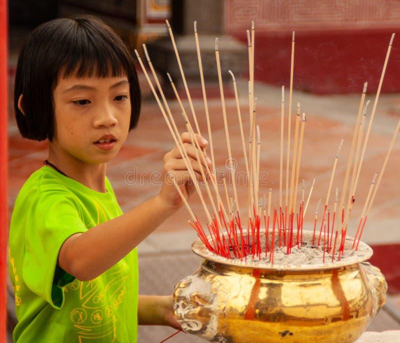 Kinesisk flicka som planterar inciense i en tempel i Malacca, Malaysia arkivfoton