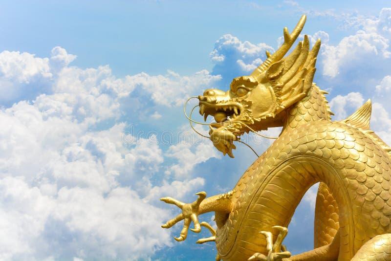 Kinesisk guld- drakestaty på moln och bakgrund för blå himmel royaltyfria bilder