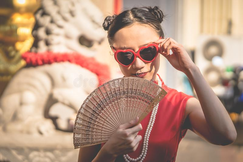 Kinesisk kvinna med solglasögon med träfanen för modernt kinesiskt flickabegrepp royaltyfria bilder