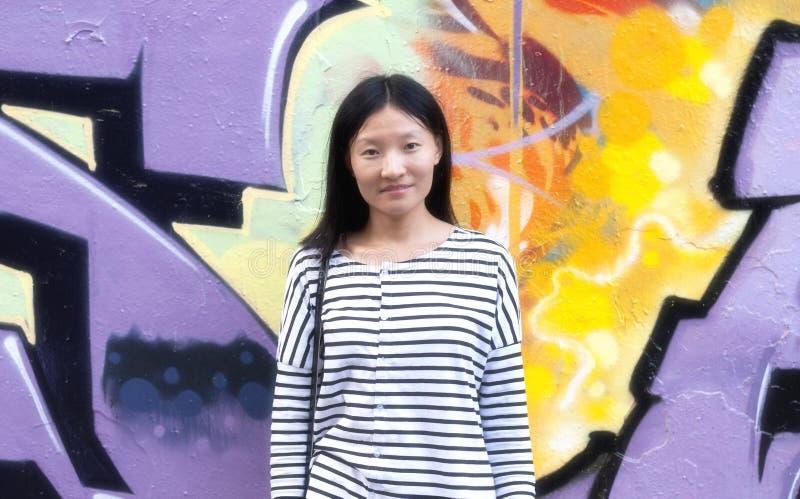 Kinesisk kvinna mot den stads- konstväggen arkivfoton