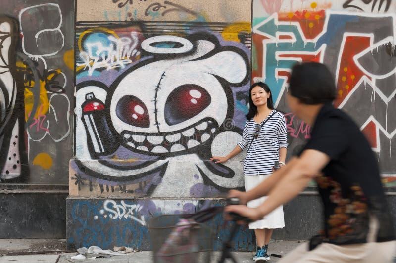 Kinesisk kvinna mot den stads- konstväggen royaltyfria foton