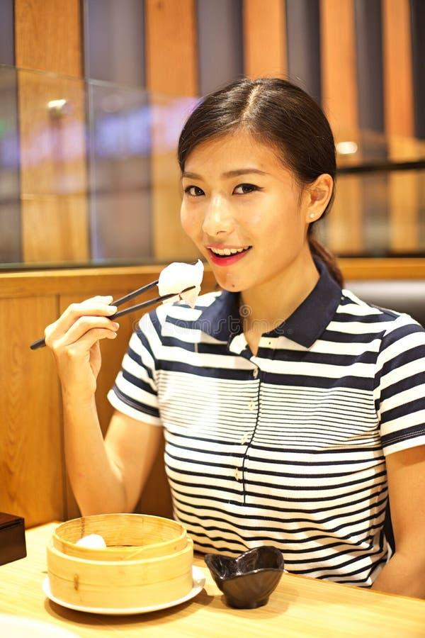 Kinesisk kvinna som äter den ångade klimpen i restaurang arkivfoton