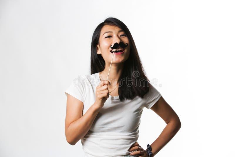 Download Kinesisk Kvinna Som Har Gyckel Med En Fejkamustasch Arkivfoto - Bild av deltagare, hand: 78732282