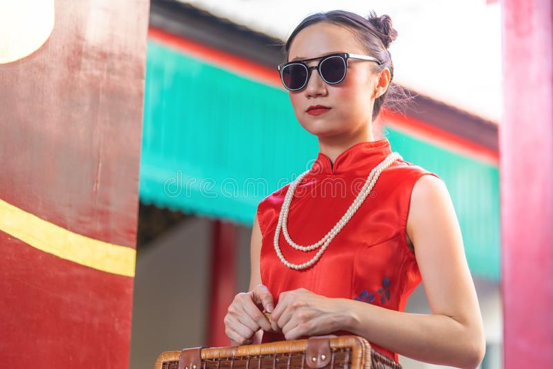 Kinesisk kvinna som rymmer en träresväska för orientaliskt loppbegrepp för tappning arkivfoto
