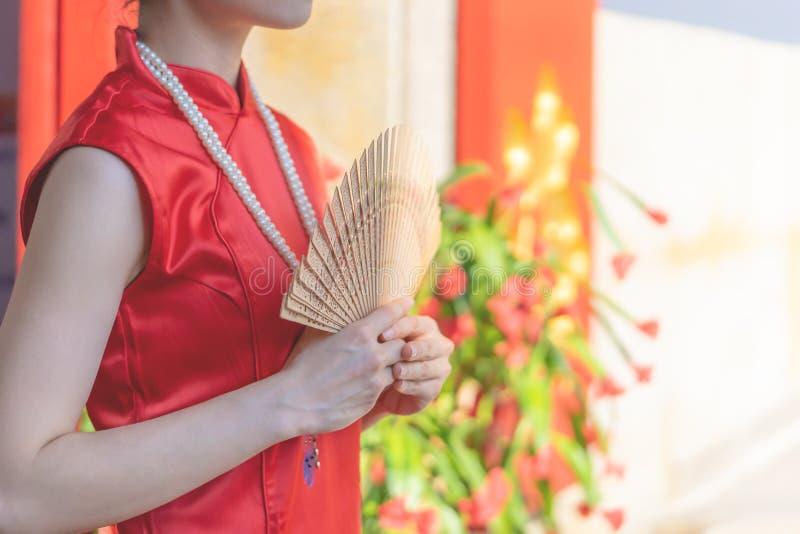 Kinesisk kvinna som rymmer träfanen för kinesiskt modebegrepp för nytt år royaltyfri foto