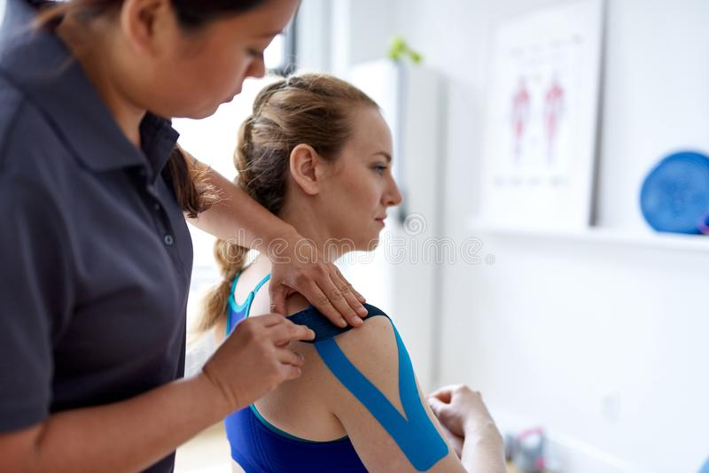 Kinesisk kvinnamassageterapeut som applicerar kinesiobandet till skuldrorna och att hångla av en attraktiv blond klient i a arkivfoton