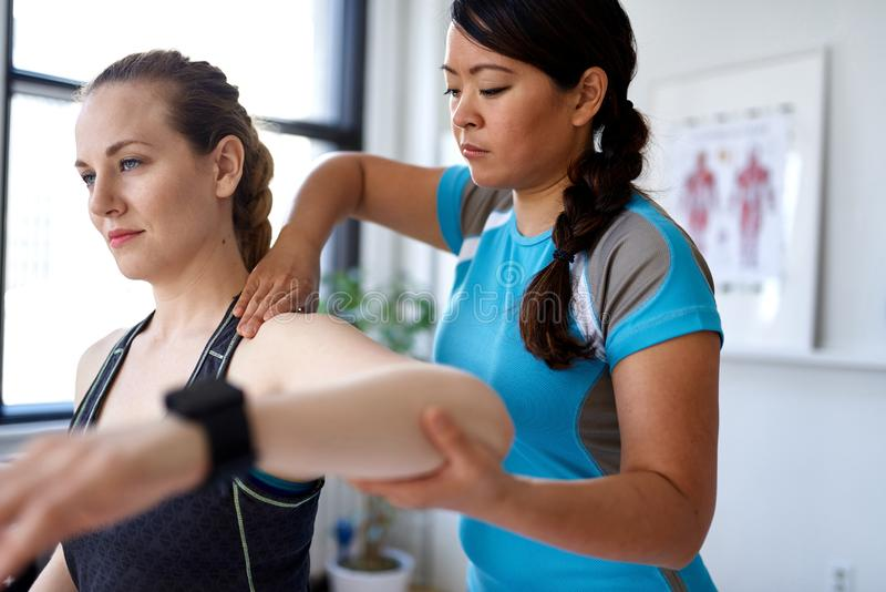 Kinesisk kvinnasjukgymnastikprofessionell som ger en behandling till en attraktiv blond klient i ett ljust medicinskt kontor arkivfoton