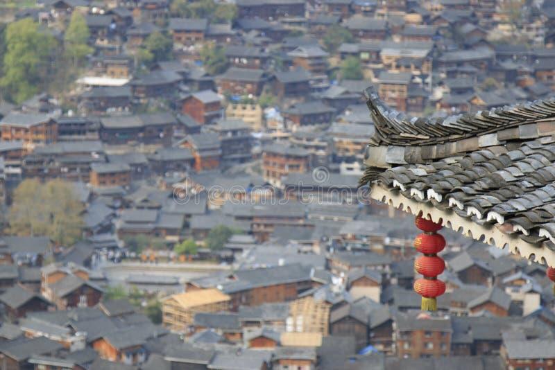 Kinesisk lykta på förgrund och Xijiang Qianhu Miao Village i Guizhou, Kina på bakgrund royaltyfri foto
