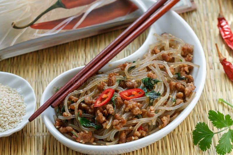 Kinesisk maträtt av stärkelseexponeringsglasnudlar ris, potatisar, bönor med köttgriskött eller nötkött arkivbild