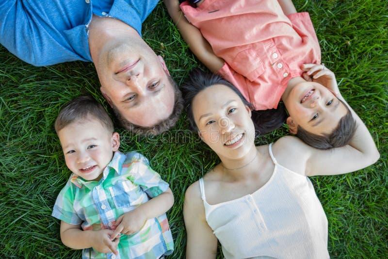 Kinesisk moder, Caucasian fader och barn för blandat lopp som lägger på gräs royaltyfri fotografi