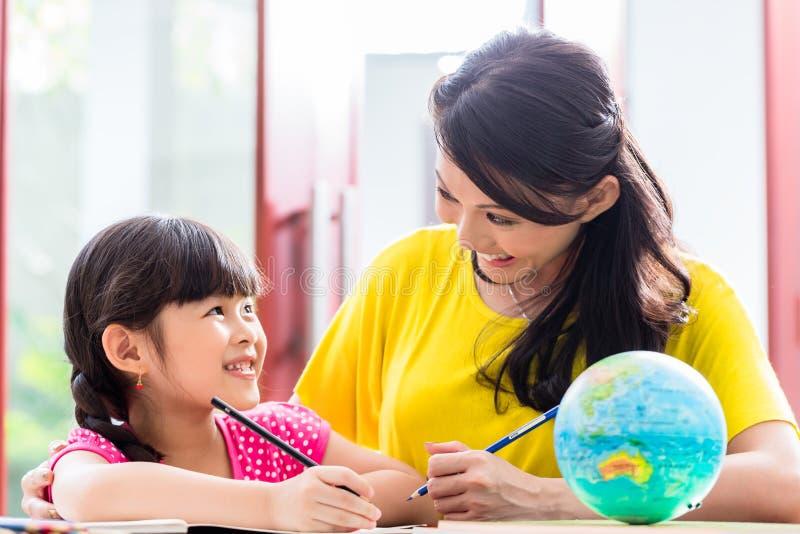 Kinesisk moder som gör skolaläxa med barnet royaltyfria bilder