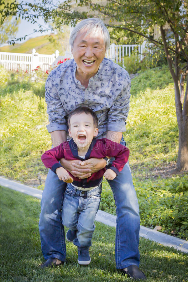 Kinesisk morfar som har gyckel med hans sonson för blandat lopp utanför royaltyfria foton