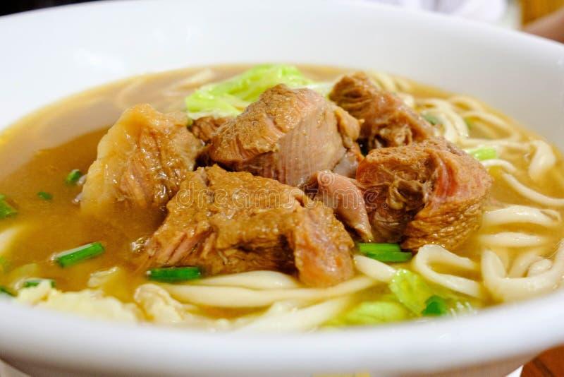 Kinesisk serve för nötköttnudelsoppa i en varm bunke stänk arkivbild