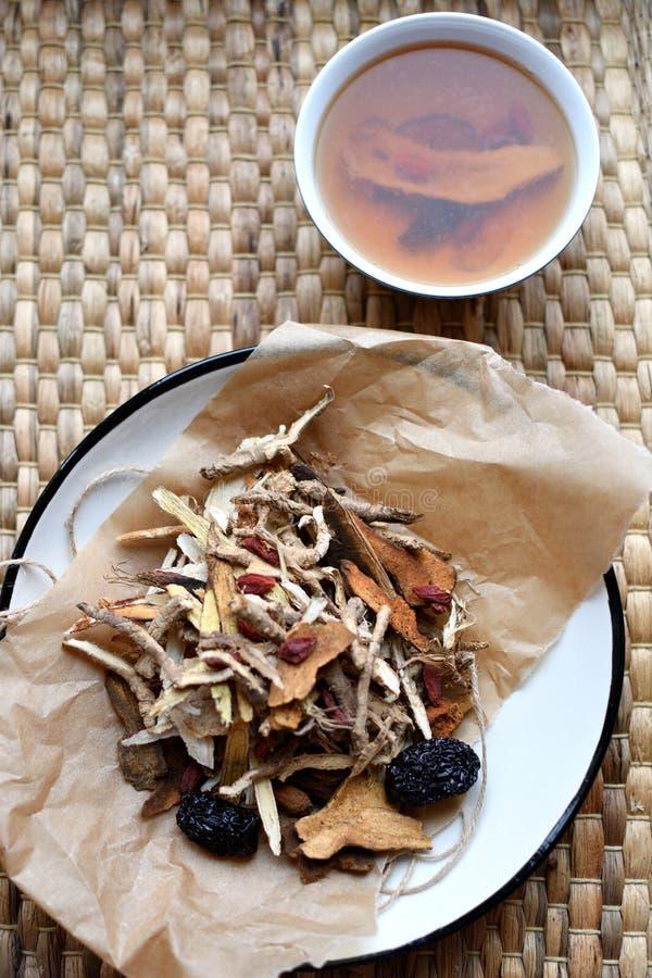 Kinesisk skrift för traditionell medicin Örtte med jujubes, gojibär, gingseng rotar och andra på pergamentpapper på neutra fotografering för bildbyråer