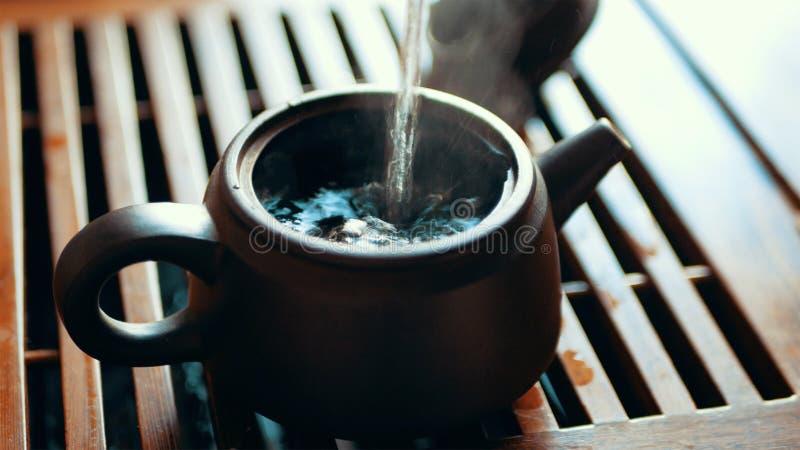 Kinesisk teceremoni med puerhte som bryggar svarta Shu Puer i kruka från Ixin lera, kokande vatten, häller in i kokkärlet, slut u royaltyfri bild