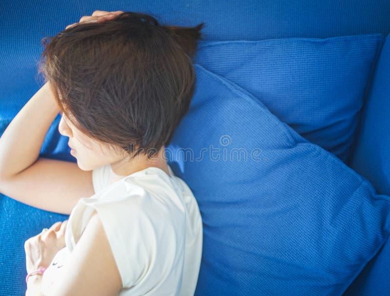 Kinesisk tonåring som tar en ta sig en tupplur på en purpurfärgad soffa arkivbilder