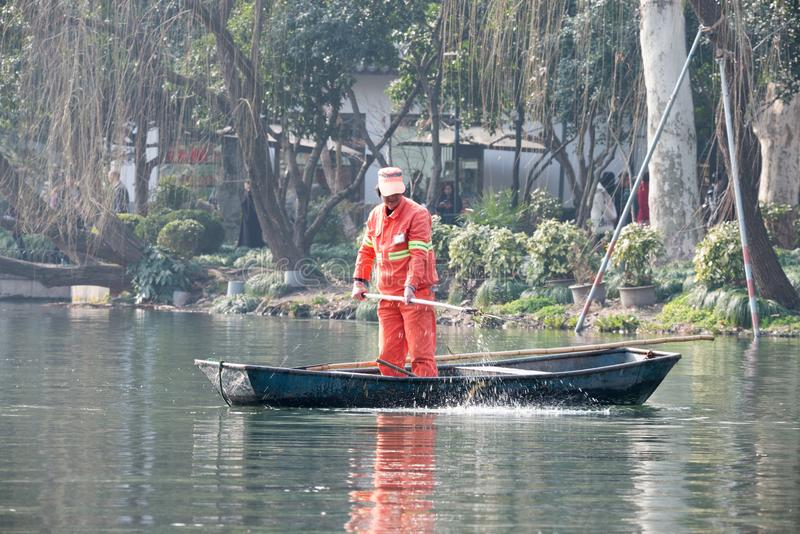 Kinesiska arbetarlokalvårdsidor från sjön vid handen, dag, fartyg som står arkivfoto
