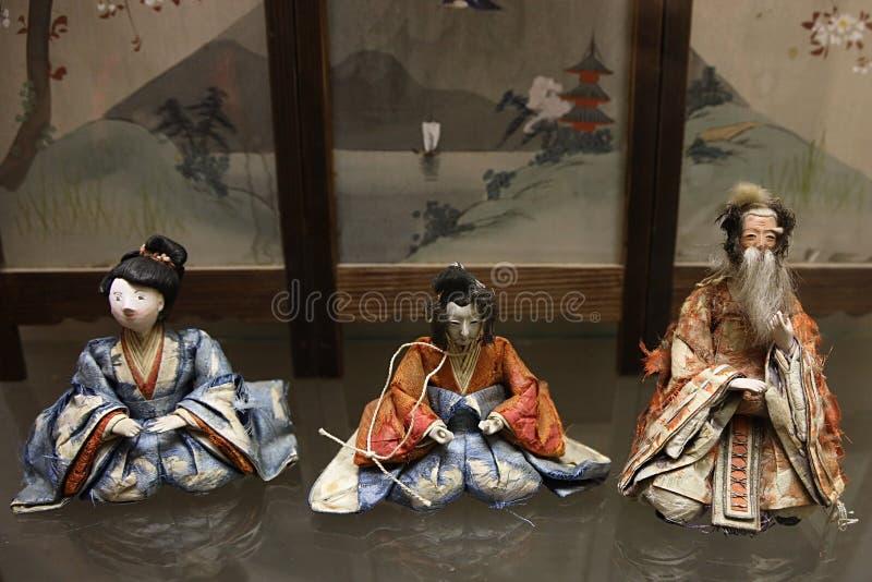 Kinesiska dockadockor, två kvinnor och äldre man som visas som utställning, kinesisk landskapbakgrund royaltyfri foto