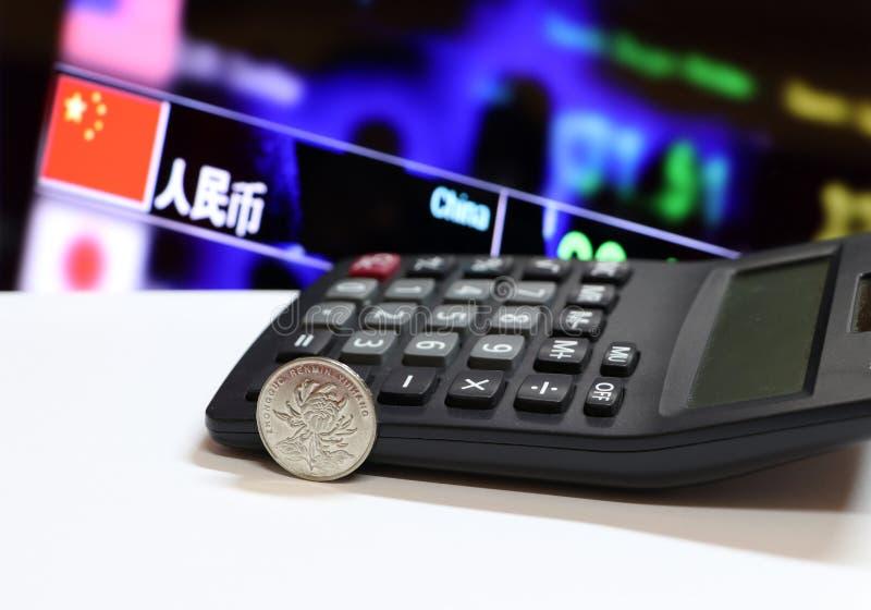 Kinesiska ett Yuan mynt på blomningen för aversCNY-krysantemum, banknamn ZHONGHUA RENMIN YINHANG på det vita golvet och räknemask royaltyfria foton