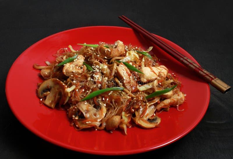 Kinesiska Glass nudlar, anbudhönafilé, grönsaker, champignons, ingefära och soya, salladslökar, sesam på en röd platta royaltyfri fotografi