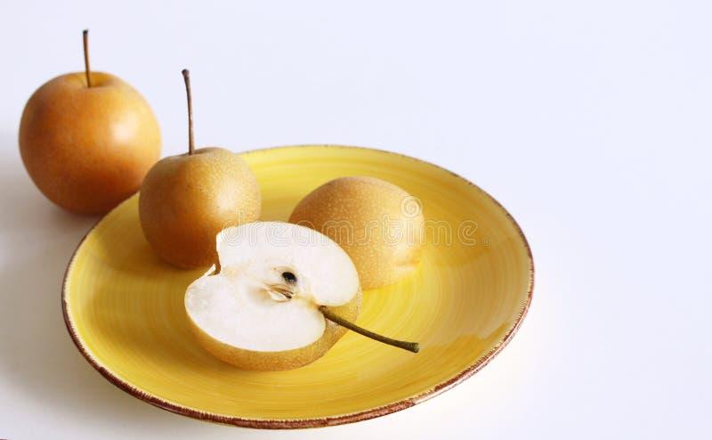 Kinesiska guld- päron i en porslinbunke Nashi variation som isoleras på vit bakgrund olivgrön för olja för kök för kockbegreppsma arkivbilder