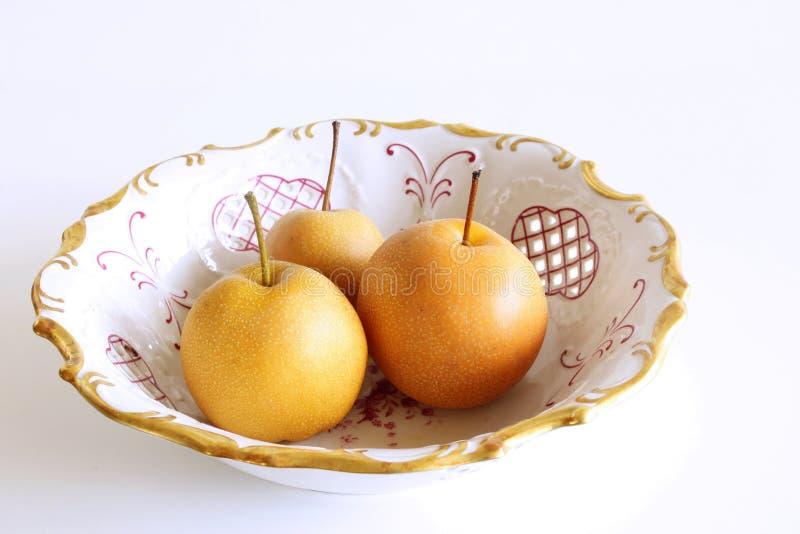 Kinesiska guld- päron i ett porslin bowlar Nashi variation som isoleras på vit bakgrund olivgrön för olja för kök för kockbegrepp arkivfoton