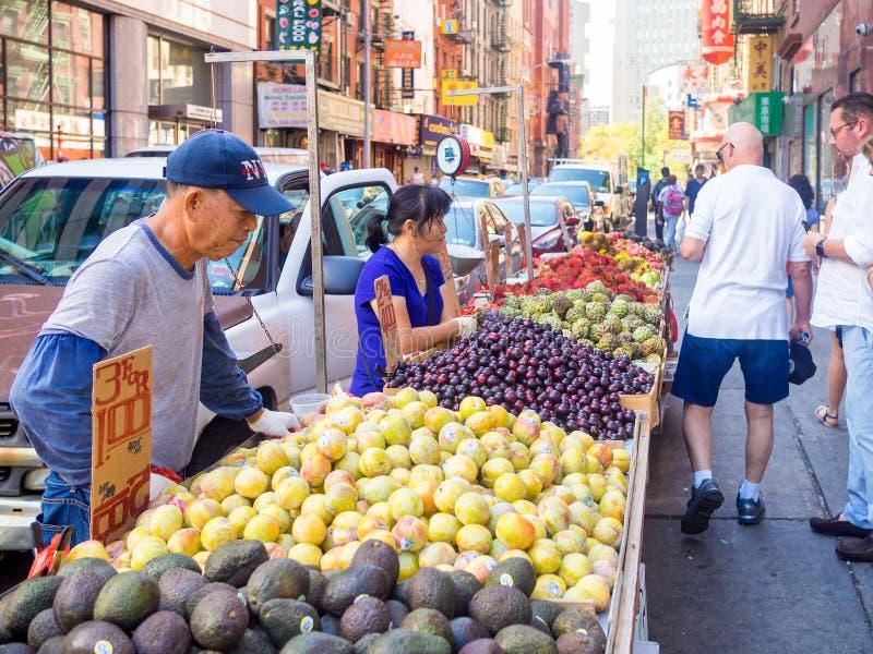 Kinesiska invandrare som säljer exotiska frukter på kineskvarteret i New York City royaltyfria bilder