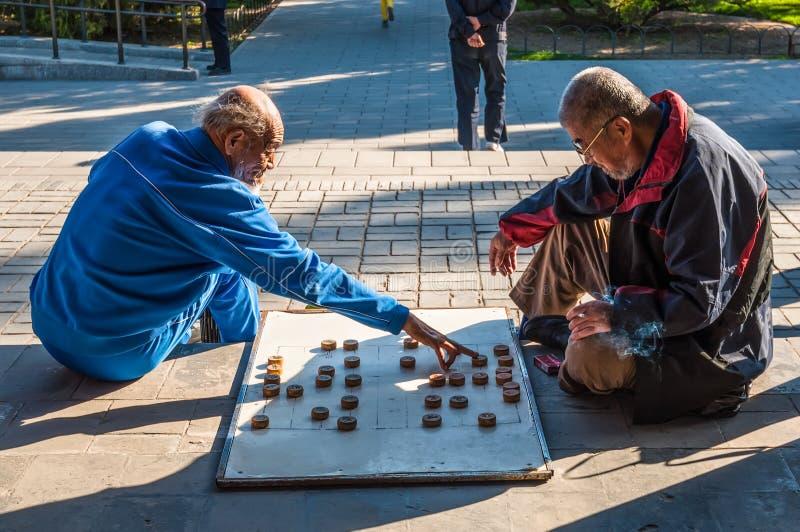 Kinesiska män som spelar kinesiskt schack, kallade Xiangqi arkivfoton