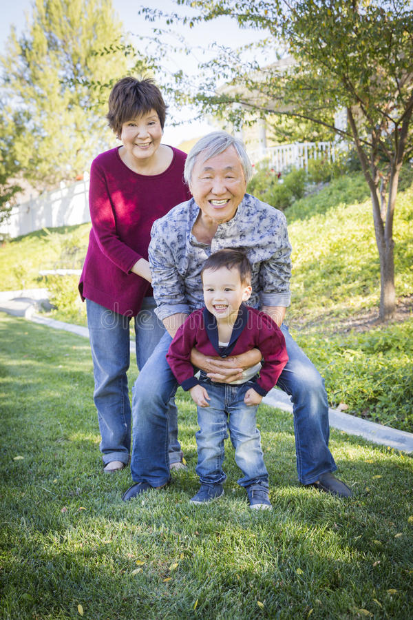 Kinesiska morföräldrar som har gyckel med deras sonsonnolla för blandat lopp royaltyfria bilder