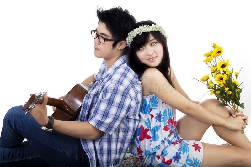 Kinesiska par som spelar den isolerade gitarren arkivfoton