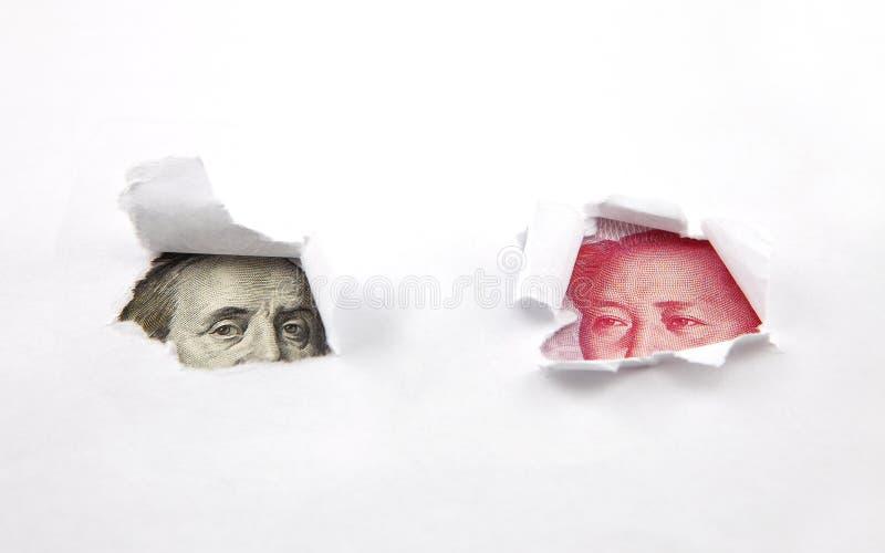 Kinesiska pengar och dollar bak två hål i papper arkivfoton