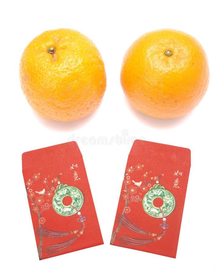 Kinesiska röda kuvert och ett par av mandariner för mån- berömmar för nytt år arkivbild