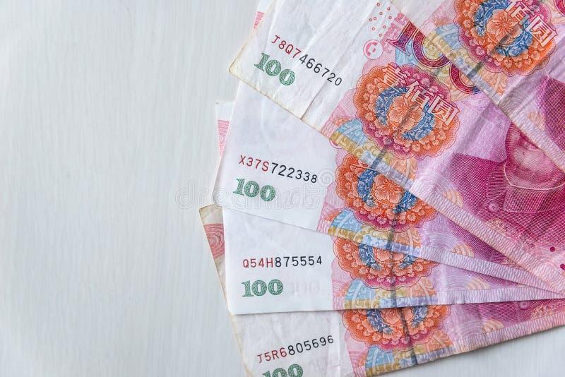 Kinesiska sedlar 100 yuan i fan på trätabellen royaltyfria foton