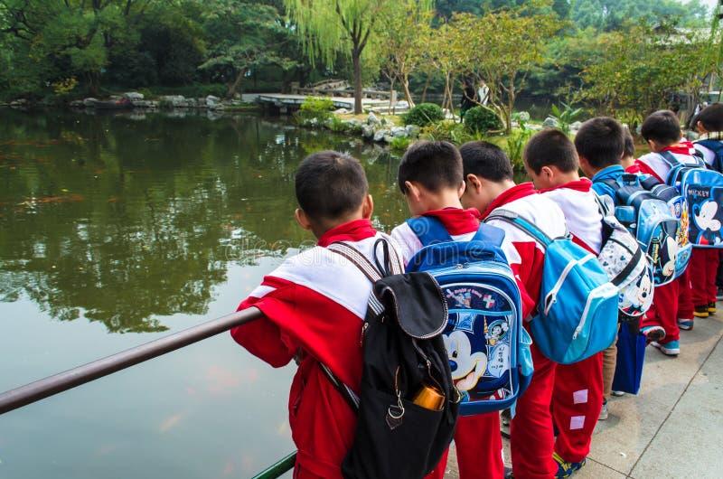 Kinesiska skolbarn i blommahamnen parkerar royaltyfri foto