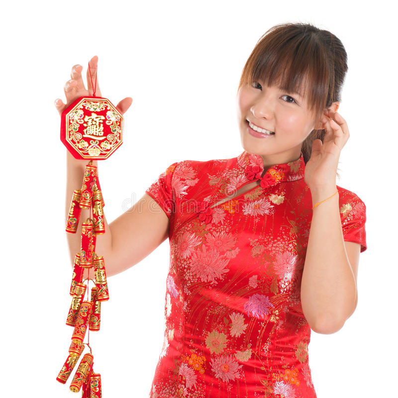 Kinesiska smällare för hållande brand för cheongsamflicka royaltyfri fotografi