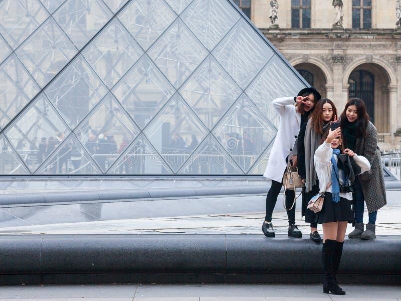 Kinesiska turister som framme tar selfiefoto av Louvrepyramiden Louvrepyramiden är en av de huvudsakliga dragningarna av Paris royaltyfri bild