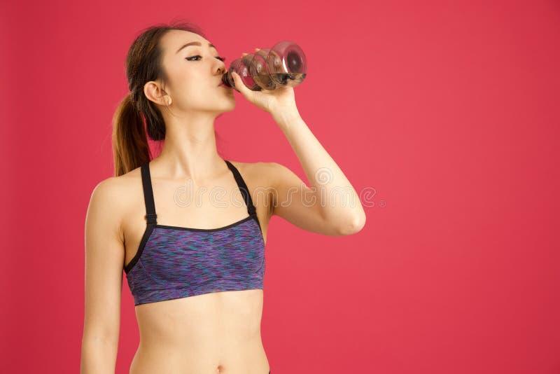 Kinesiskt flickadricksvatten ut ur flaskan i rosa bakgrund royaltyfri foto